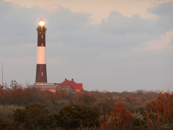 Fire Island Lighthouse tower with pink glow from setting sun.