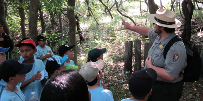 A park ranger points to trees in the Sunken Forest on a tour with school children.