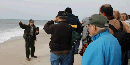 Ranger presents talk to group on beach.