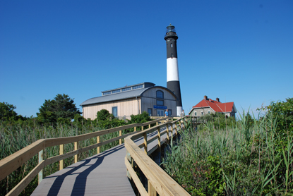 Boardwalk leads to new Fresnel Lens Building with Fire Island Lighthouse and its keepers quarters beyond.