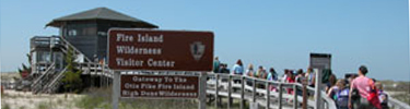 Group of students pass park sign as they walk down boardwalk to the Wilderness Visitor Center.