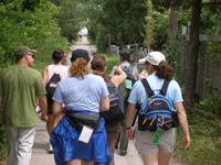 Group of hikers stroll down narrow walkway through Fire Island Community.