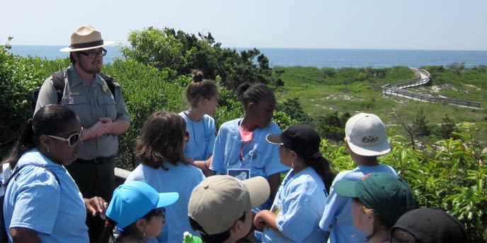 A park ranger talks to a group of students atop a platform in the Sunken Forest.