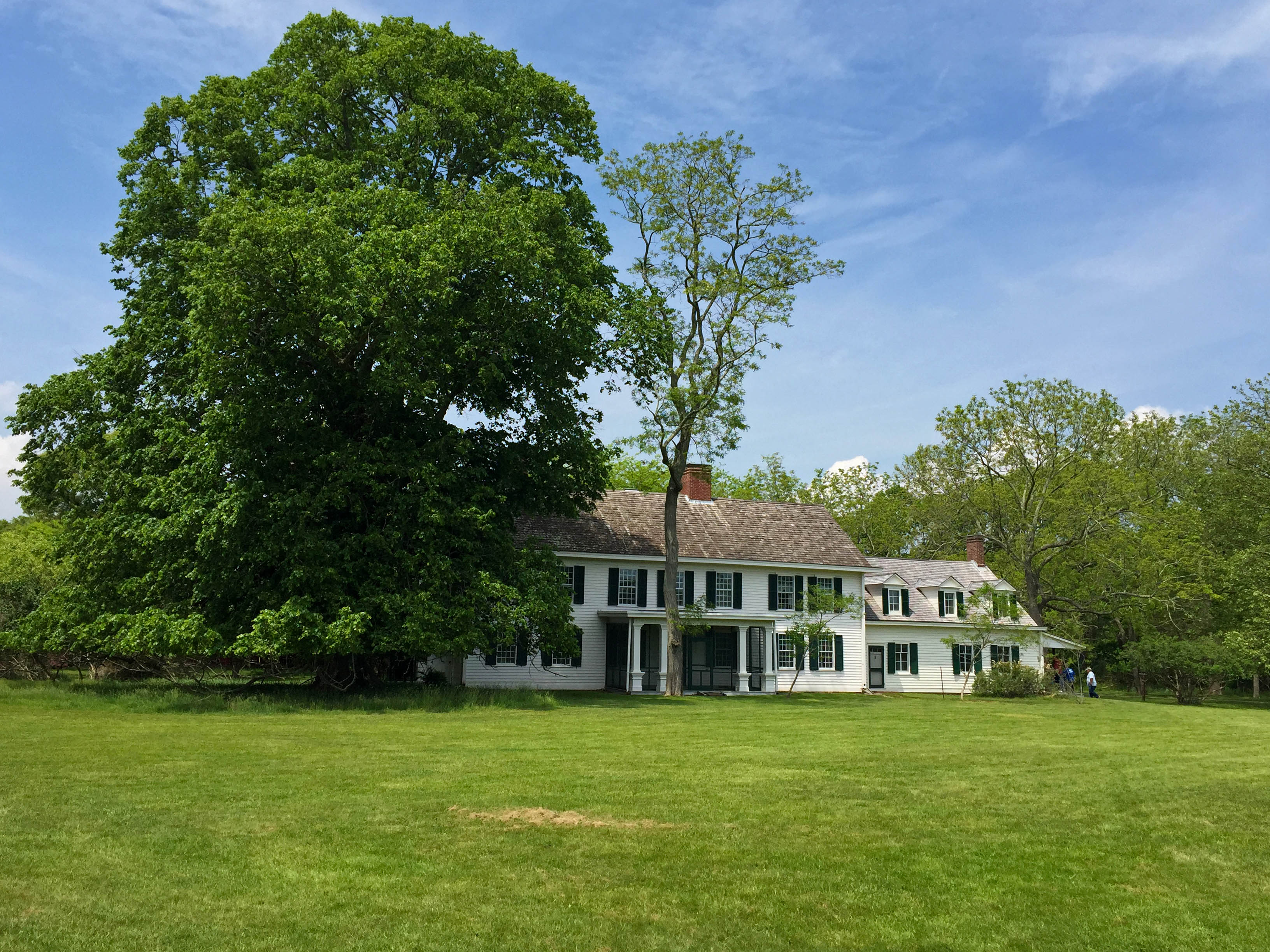 View of large, white historic home from lush green field.