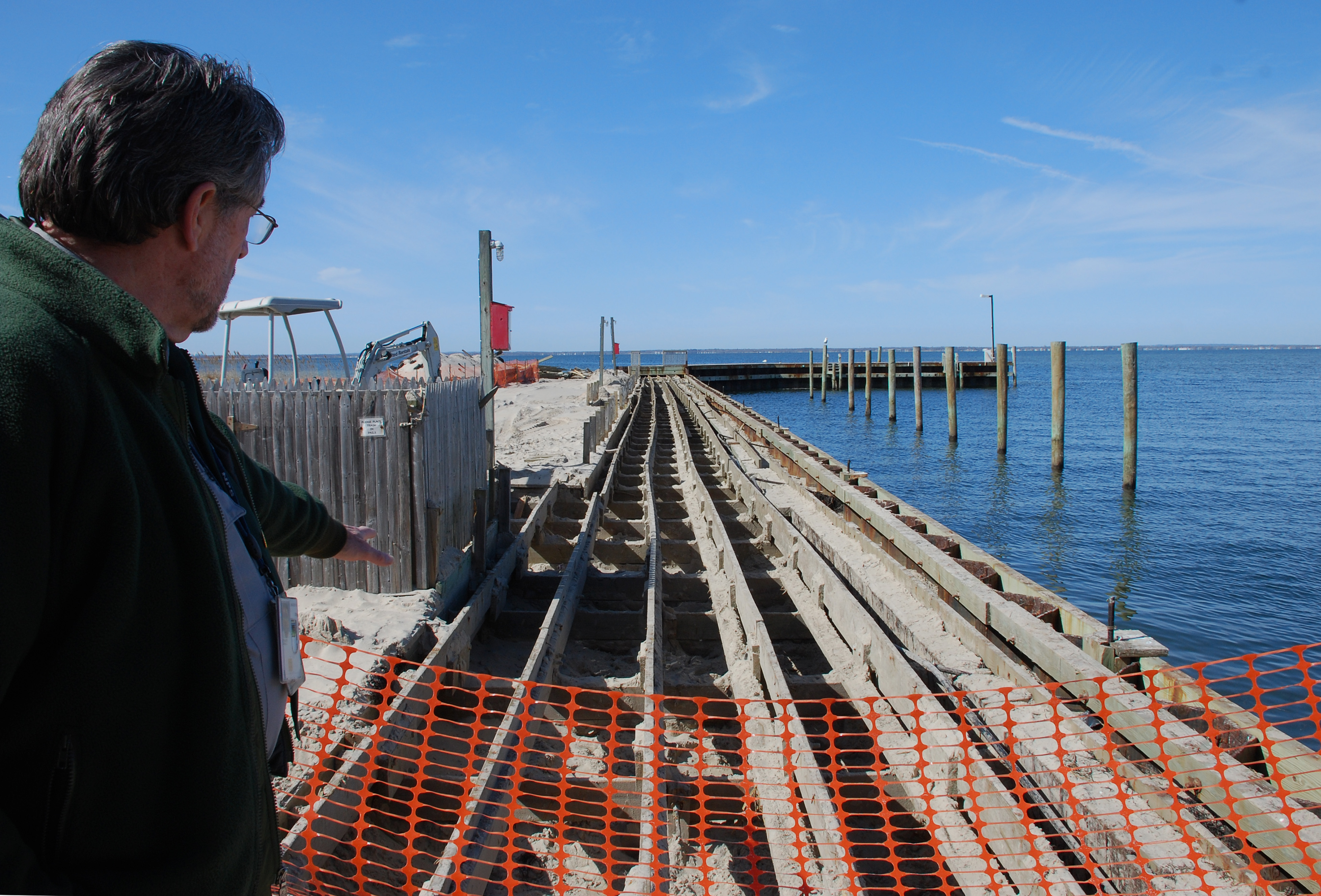Superintendent Chris Soller points to substructure of Sailors Haven marina.