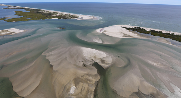 Looking down from the sky, sand swirls just below the ocean surface around sandy islands with light vegetation.