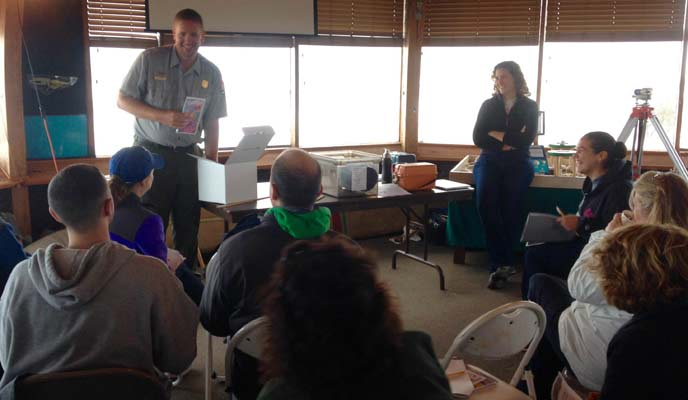 A park ranger introduces an educational activity to a group of teachers.