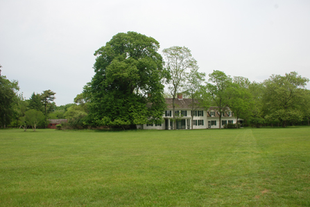 William Floyd Estate Grounds and Old Mastic House flanked by towering trees.