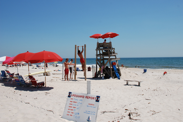 Lifeguards on duty in stands, under red umbrellas, and on chin-up bar at Sailors Haven beach.