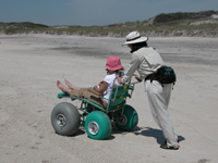 Woman pushing another person sitting in large-tired beach wheel chair.