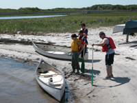 Canoeists prepare to board vessels on calm bay shoreline.