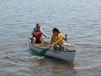 Two canoeists paddle a small canoe on calm bay water.
