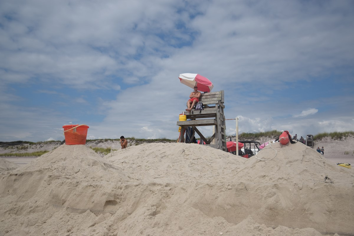 A lifeguard sits in a lifeguard chair on a sandy beach.