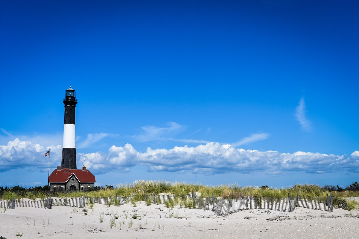 View From Beach Of Black And White Lighthouse Tower Keepers Quarters With Red Roof