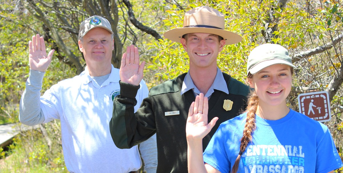 An intern, park ranger, and volunteer raise their hand to take the Fire Island Pledge.
