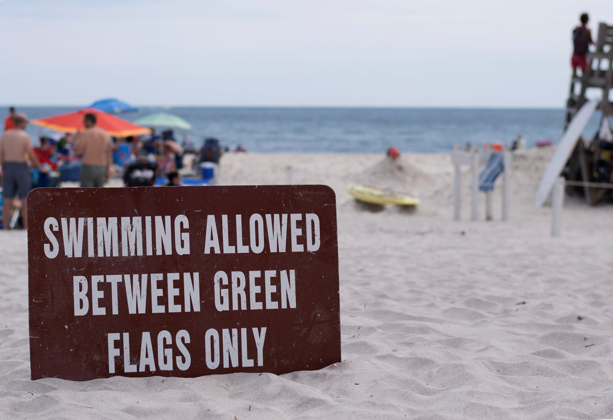 "A sign reading, ""Swimming allowed between green flags only"" sits in the sand near a lifeguarded beach."