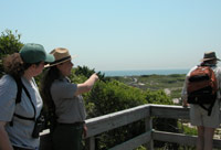 Ranger on overlook points to ocean in the distance.