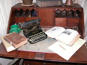 Antique typewriter on desk with open books.