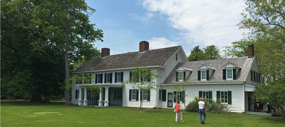 Visitors walk across the lawn in front of the historic Old Mastic House at the William Floyd Estate.