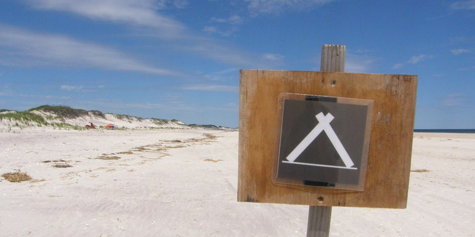 A campground sign on the beach.
