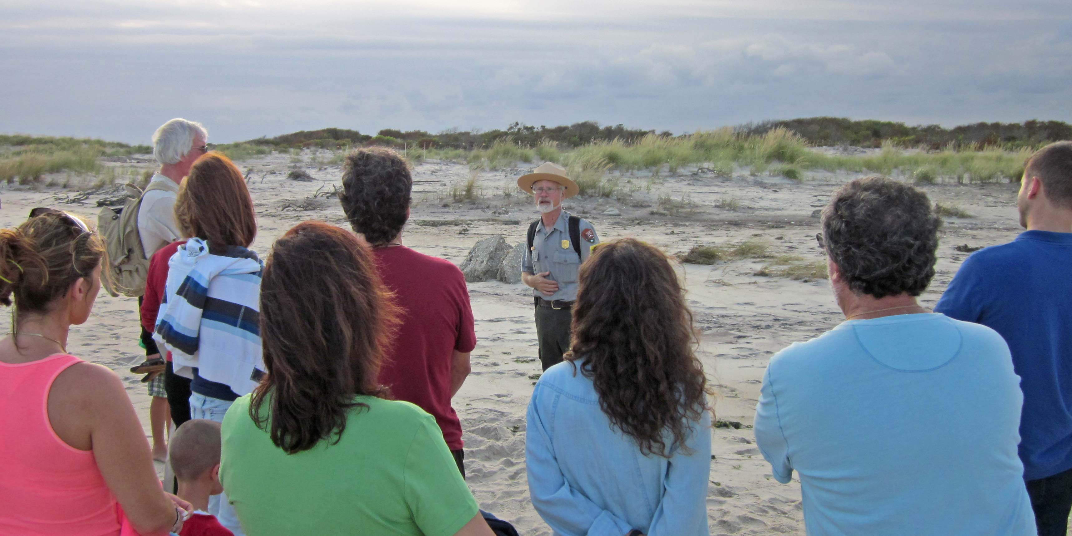 A park ranger leads a group on a hike to the breach at Old Inlet