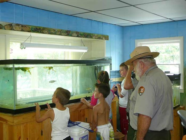 Children explore the fish tank at Sailors Haven Visitor Center.