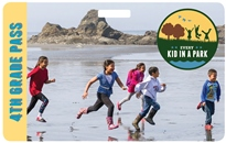 2016 4th Grade Pass with five children running on beach with large rocks in background