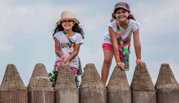 Two girls smile from a wooden fence