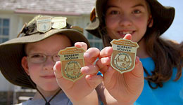 Two kids show their Junior Ranger badges