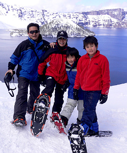 Family of four posing on showshoes in front of Crater Lake