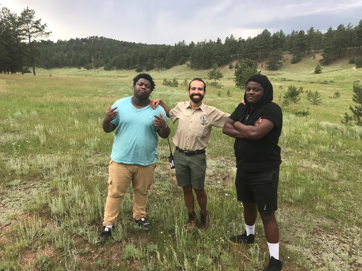 Education Intern, Kevin Jauregui stands next to hip hop artists Nehemiah Vaughn and Joey Lovett in a grassy meadow at Florissant Fossil Beds.