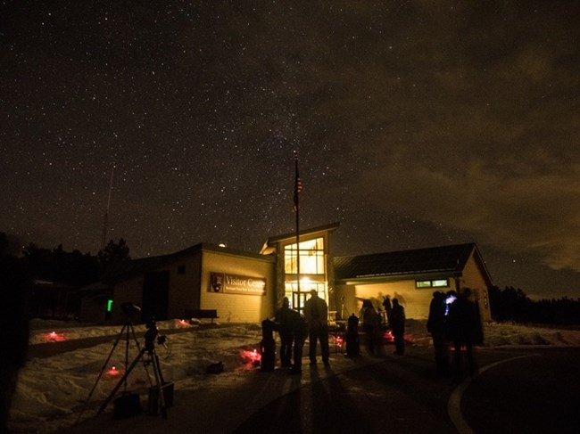 Visitors looking at the night skies through telescopes in front of the Visitor Center at Florissant Fossil Beds