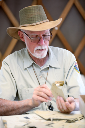 Volunteer Dr. Bob Carnein demonstrates splitting shale.