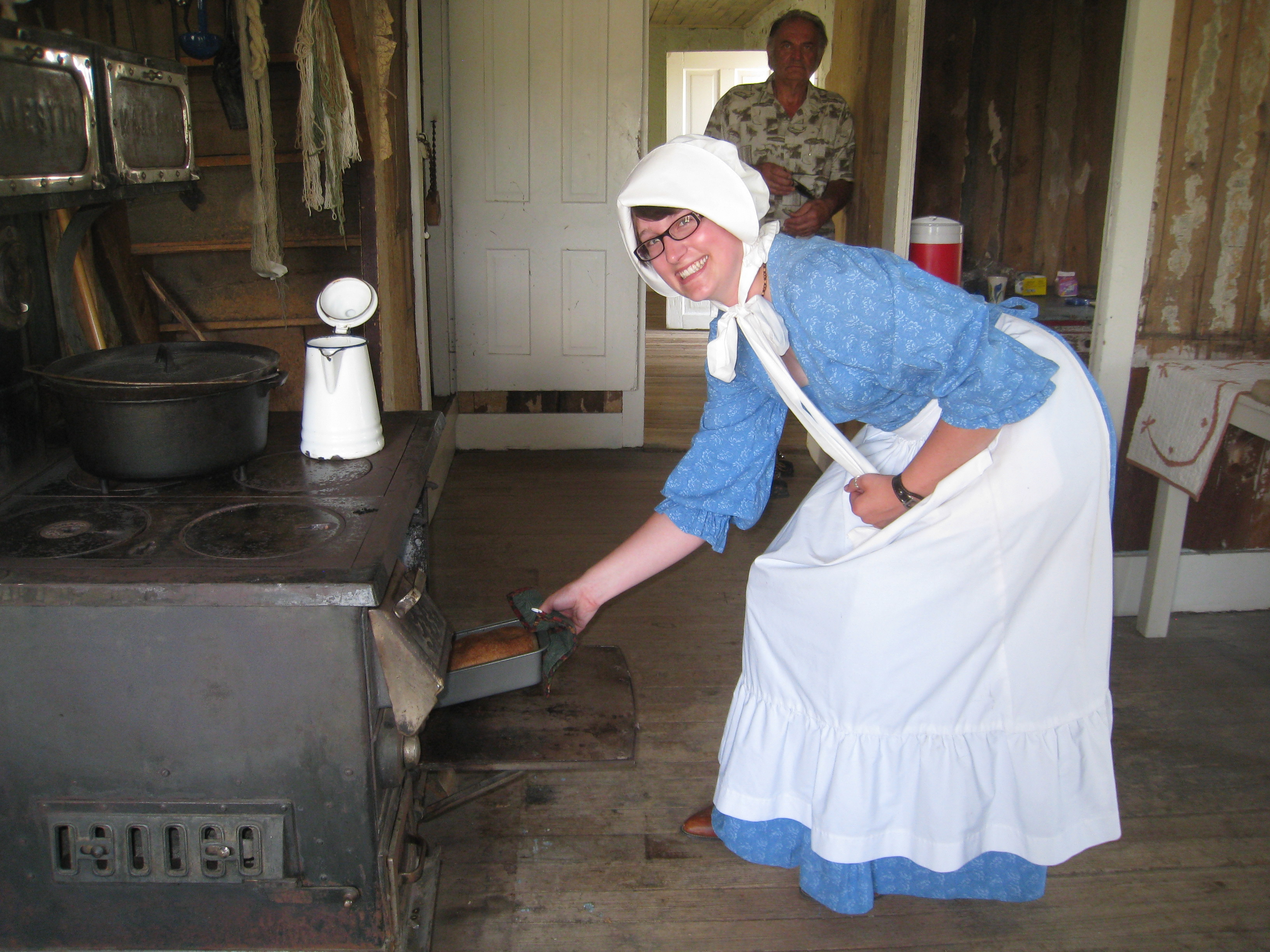 Park staff, dressed in late 1800s clothing, prepare fresh bread in the woodstove