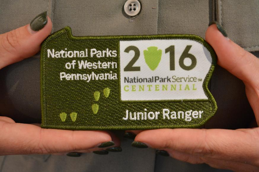 Patch in the shape of Pennsylvania.  Green with white lettering and small lighter green arrowhead shapes.  Writing:  National Parks of Western Pennsylvania Junior Ranger.