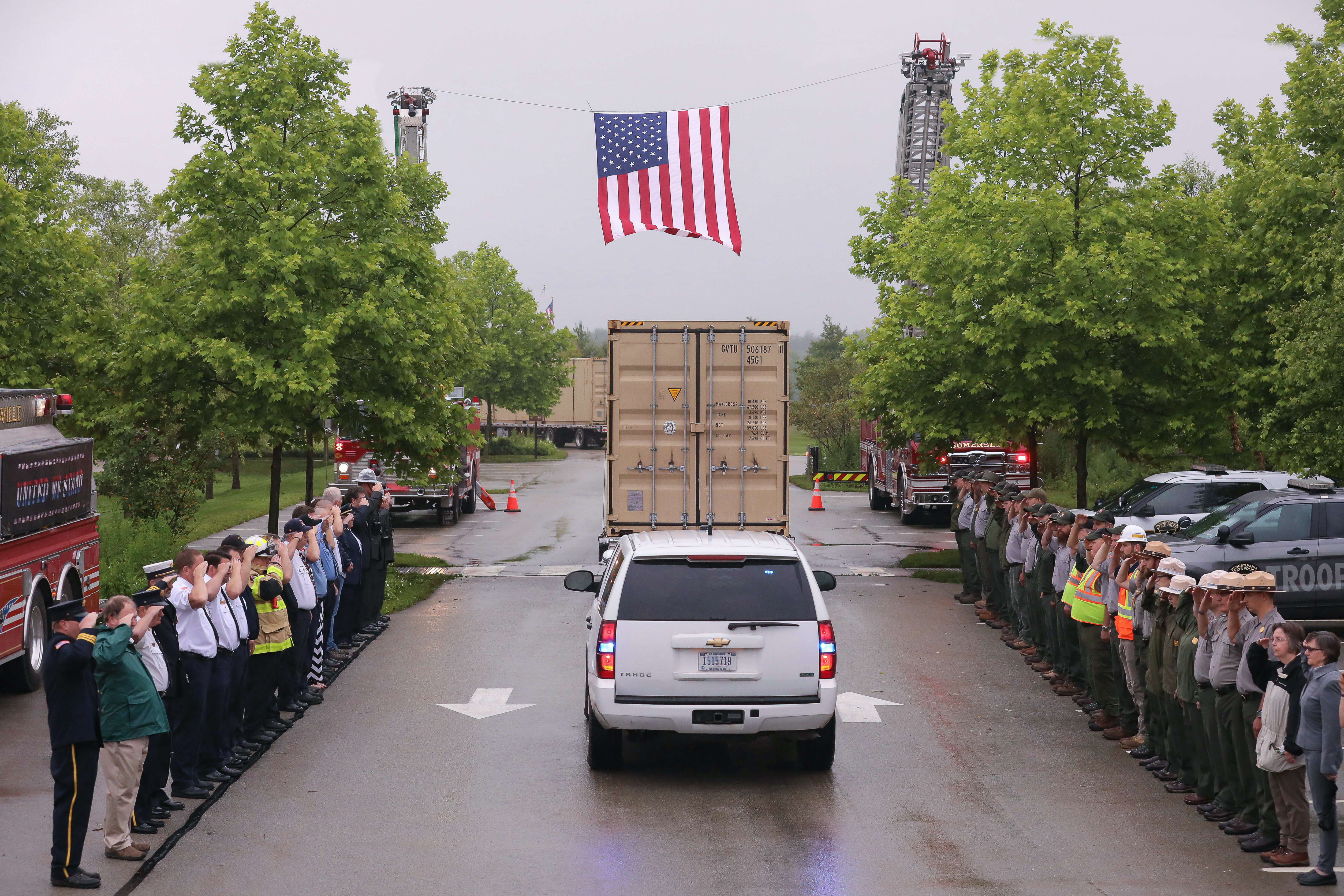 Flatbed truck with a large shipping container drives under a suspended American flag as onlookers salute.