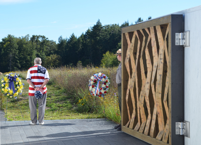 man in flag shirt standing past wooden gate looking at a field