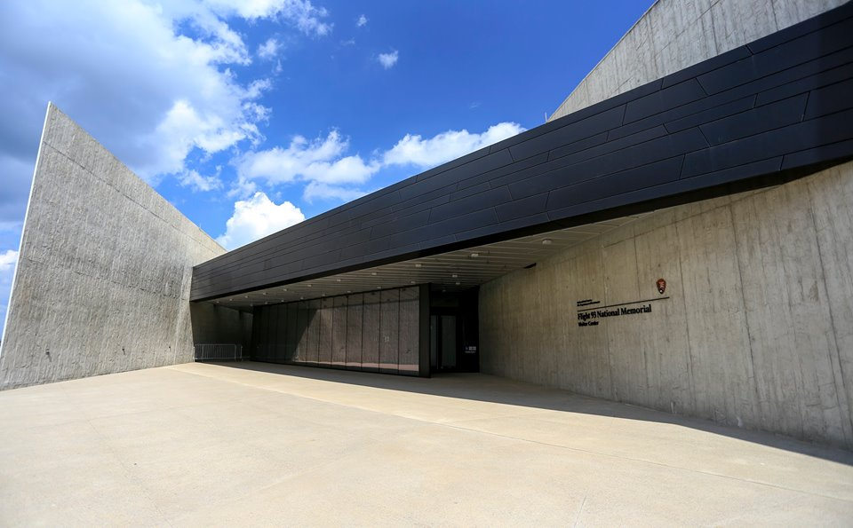 Building entrance - tall gray concrete walls , black metals, and glass