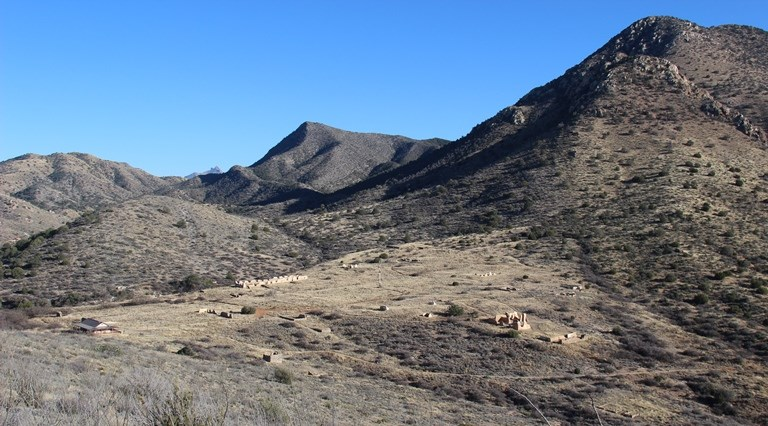The remains of Fort Bowie on a clear day in a mountain pass.