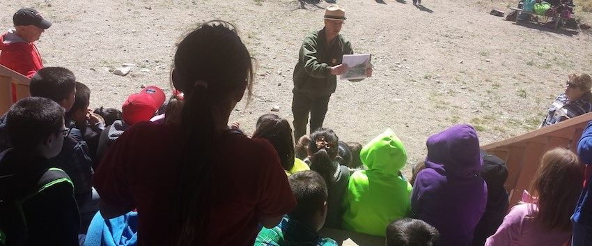 A ranger shows a picture to a group of young students