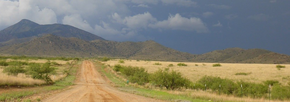 A dirt road stretches into the mountains under stormy skies