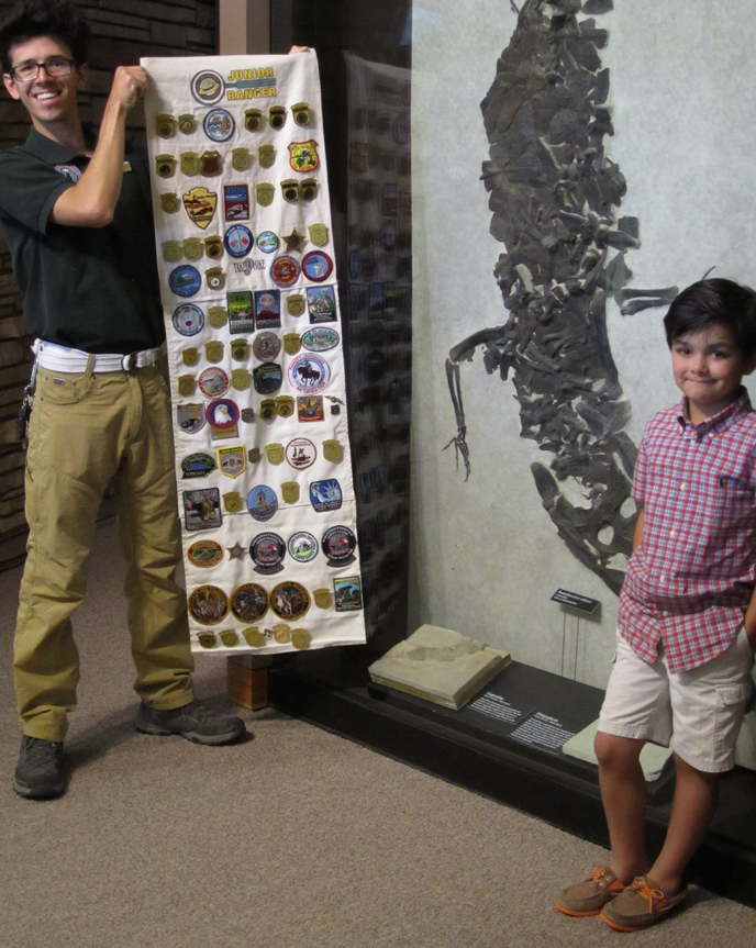 Matthew, age 7, a proud Jr. Ranger of several NPS sites stands with Andy, a GeoCorps Intern