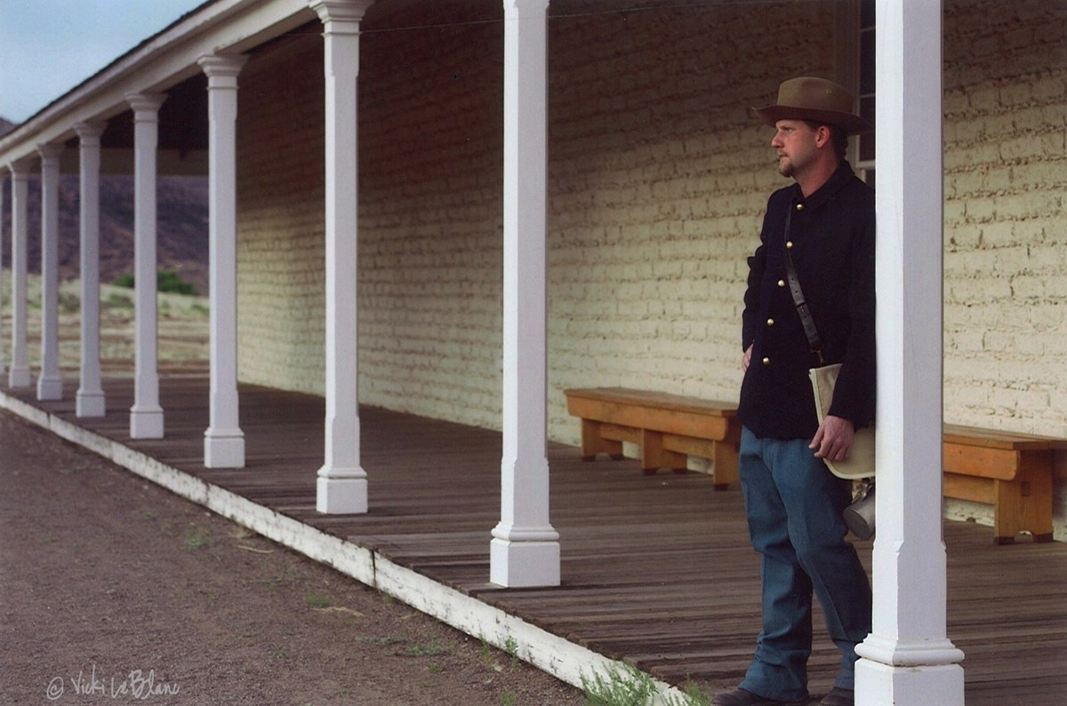 Soldier standing in front of barracks leaning on column