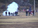 Picture of a volunteers in period dress firing the post cannon during flag lowering ceremony.