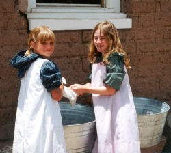 A couple of young girls in living history apparel washing clothes in front  of the restored kitchen.