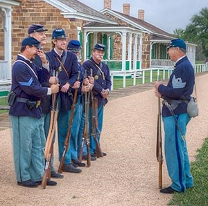 Men in 19th century U.S. Army uniforms lined up in front of sandstone quarters.