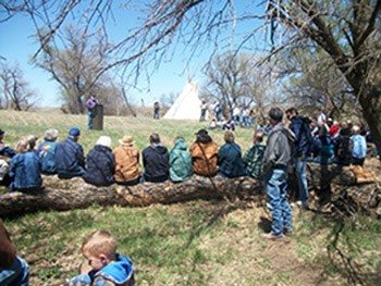 Group of people listening to a talk outside with a teepee in the background.