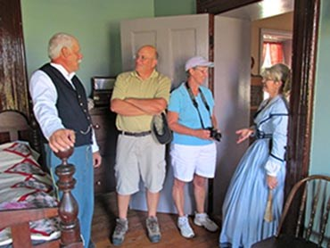 Volunteers in period clothes talking to visitors.