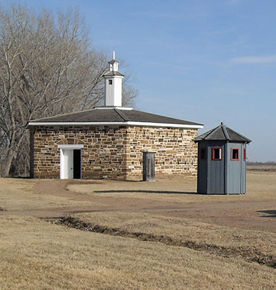 Reconstructed sandstone blockhouse with wooden sentry box in foreground.