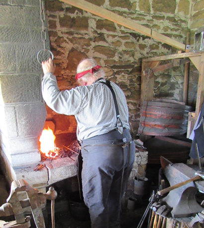 Man working at blacksmith forge.